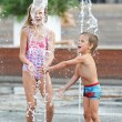 Happy children playing in a fountain — Stock Photo #52936667