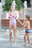 Happy children playing in a fountain — Stock Photo