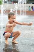 Happy kid playing in a fountain — Stock Photo