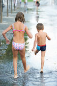 Children marching through a puddle — Stock Photo