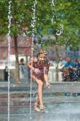 Happy girl playing in a fountain — Stock Photo
