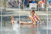 Children playing in puddle on hot weather — Stock Photo