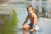 Little boy playing with water in a puddle — Stock Photo