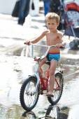 Little boy rides his bike among puddles — ストック写真