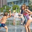 Happy children playing in a fountain — Stock Photo #56517109