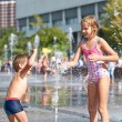 Happy children playing in a fountain — Stock Photo #56517197