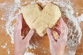 Woman holding dough heart — Stock Photo