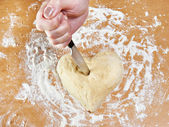 Hand with knife struck heart of dough — Stock Photo