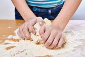 Kneading dough on girl hands — Stock Photo