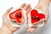 Jelly heart-shaped cakes in hands of lovers — Stock Photo