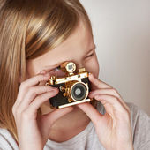 Girl photographer with gold retro camera — Stock Photo
