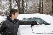 Driver with brush cleans car from snow — Stockfoto