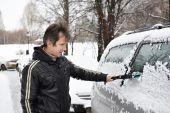Stuurprogramma met borstel reinigt auto van sneeuw — Stockfoto