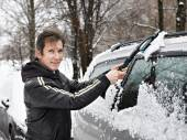Driver with brush cleans car from snow — Stock Photo