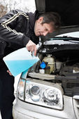 Male driver fills antifreeze liquid in washer window — Stock Photo