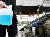 Male driver and antifreeze liquid in washer window — Stock Photo