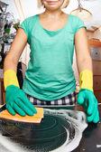 Joven de limpieza de la estufa en la cocina — Foto de Stock