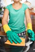 Mladá žena čištění kamen v kuchyni — Stock fotografie