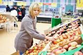 Young woman chooses apples — Стоковое фото