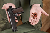 Soldier demonstrates Colt pistol and cartridges to it — Stock Photo