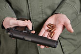 Soldier holding gun Colt and cartridges — Stock Photo
