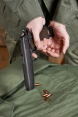 Soldiers load clip with cartridges into gun Colt — Stock Photo