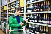 Man choosing wine in supermarket — Photo