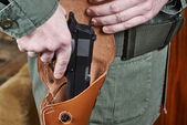 Soldier takes out gun from the holster — Stock Photo