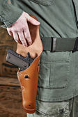 Soldier opens pistol holster — Stock Photo