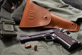 Colt pistol, holster and belt lie on military jacket — Stock Photo