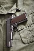 Colt pistol lie on military jacket — Stock Photo