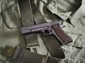 Colt gun pistol and belt lie on military jacket — Stock Photo