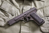 TT russian pistol and belt lie on military jacket — Stock Photo