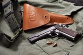 Colt gun pistol, holster and belt lie on military jacket — Stock Photo