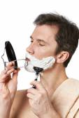 Man looks in mirror and shaving — Zdjęcie stockowe