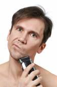 Człowiek do golenia twarzy z elektryczne maszynki do golenia — Zdjęcie stockowe