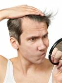Man with mirror looking at his hair — Stock Photo