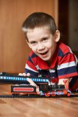 Happy boy playing with railway — Stock Photo