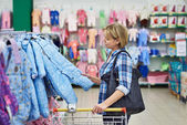Woman chooses rompers in store — Stock Photo