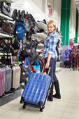 Woman chooses suitcase in shop — Stock Photo
