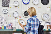 Woman chooses wall clock in store — Stockfoto