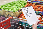 Shopping list in hands of woman in supermarket — Stock Photo