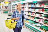 Women housewife with yellow basket shopping in dairy department — Stock Photo