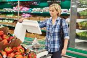 Woman weighing vegetables in supermarket — Stock Photo