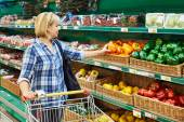 Woman buys bell peppers in store — Stock Photo