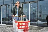 Woman with shopping cart exits the store — Stock Photo