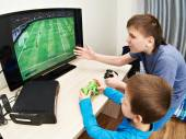 Children playing on games console to play football — Stock Photo