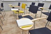 Chairs with notepads in empty classroom — Stock Photo