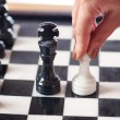 Hand with white pawn moves to black king — Stock Photo #68901995