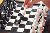 Hand with white queen hits black king — Stock Photo